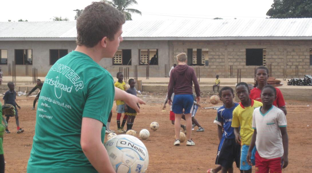 A Projects Abroad high school volunteer leads a training session to young players in Ghana.